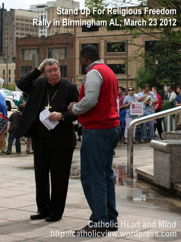 Bishop Baker speaks with a gentleman on the sidewalk at the rally
